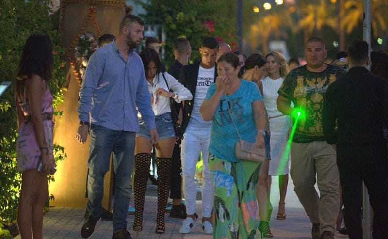 Christiano Ronaldo walking around with his bodyguard, who carries a green laser pointer to mess with photographs.