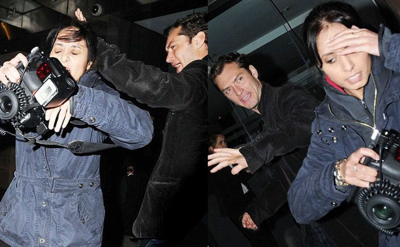 Jude Law pushing a female photographer away by her head. / Jude Law looking angry while the photographer walks away, holding her head.