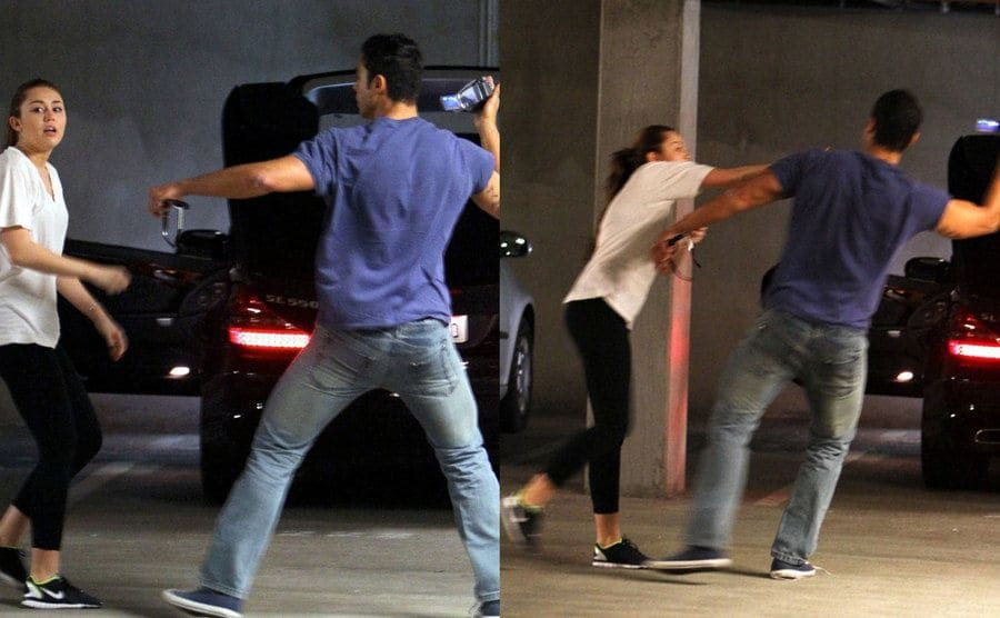 Miley Cyrus trying to take the camera away from the paparazzi near her car.