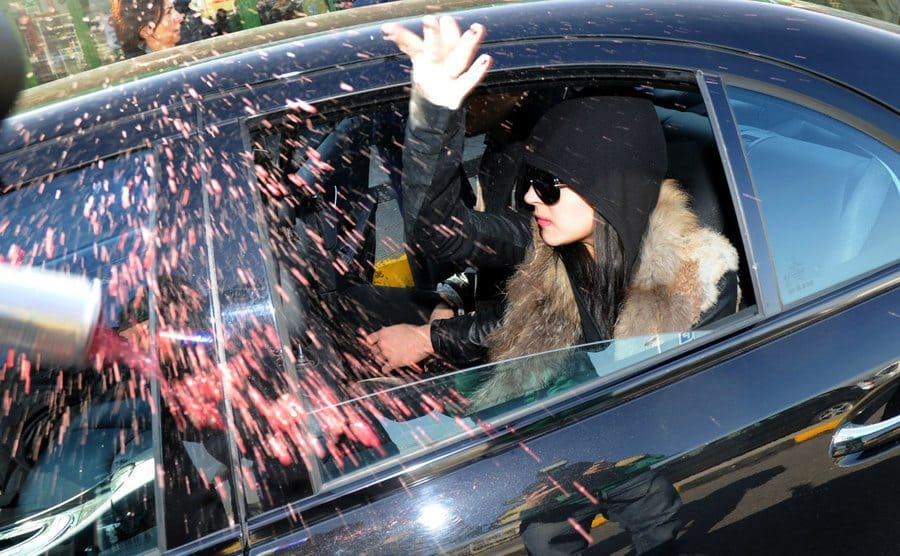 Lindsay Lohan throwing an open can of red bull out of her car window towards the paparazzi