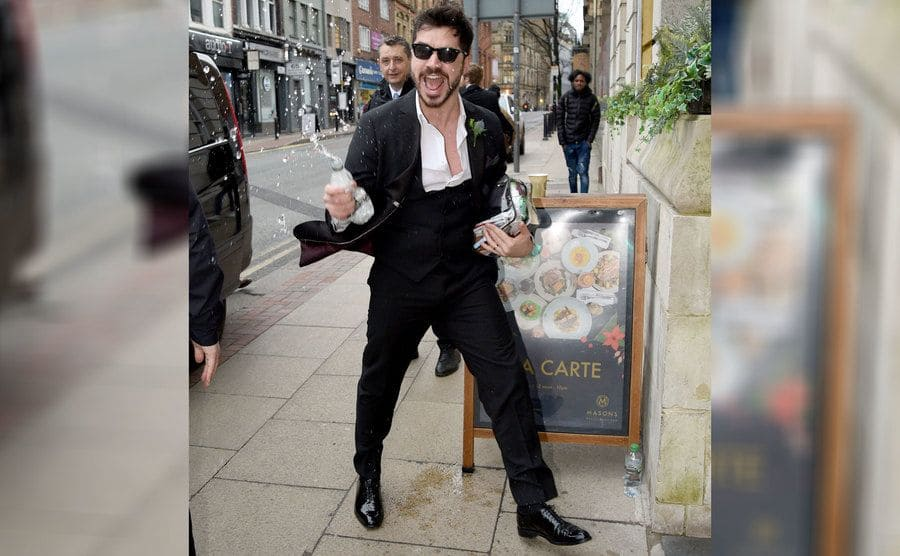 Sam Robertson soaking the paparazzi with water as he arrives for filming.