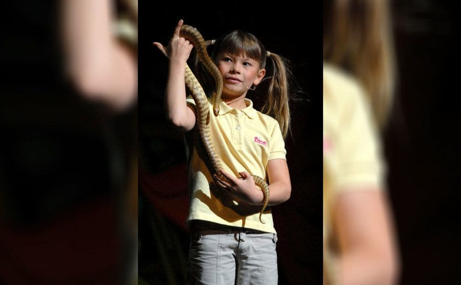 Bindi Irwin as a young girl on stage with a snake