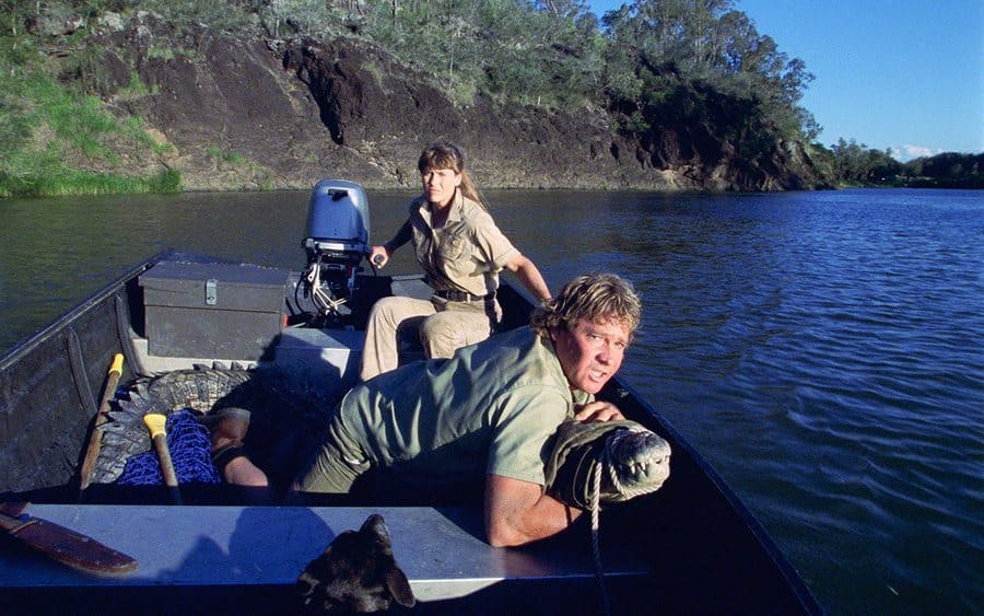 Steve Irwin holding down a crocodile in a boat while his wife, Terri, steers from the back