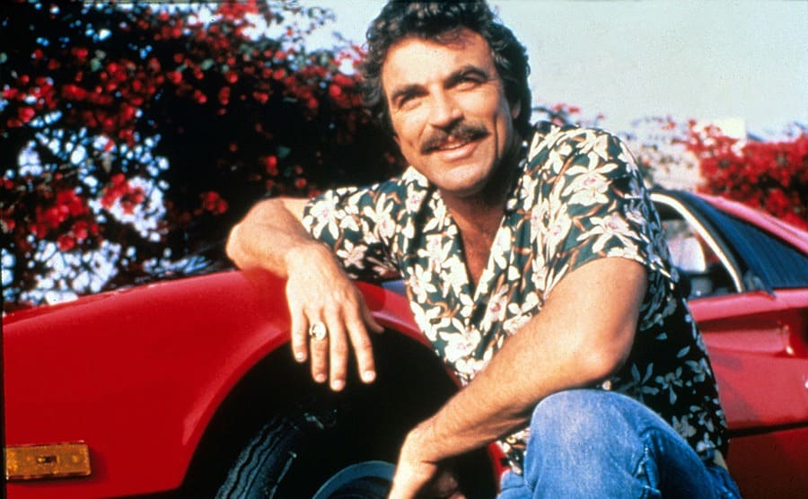 Tom Selleck wearing a Hawaiian shirt in front of a red car