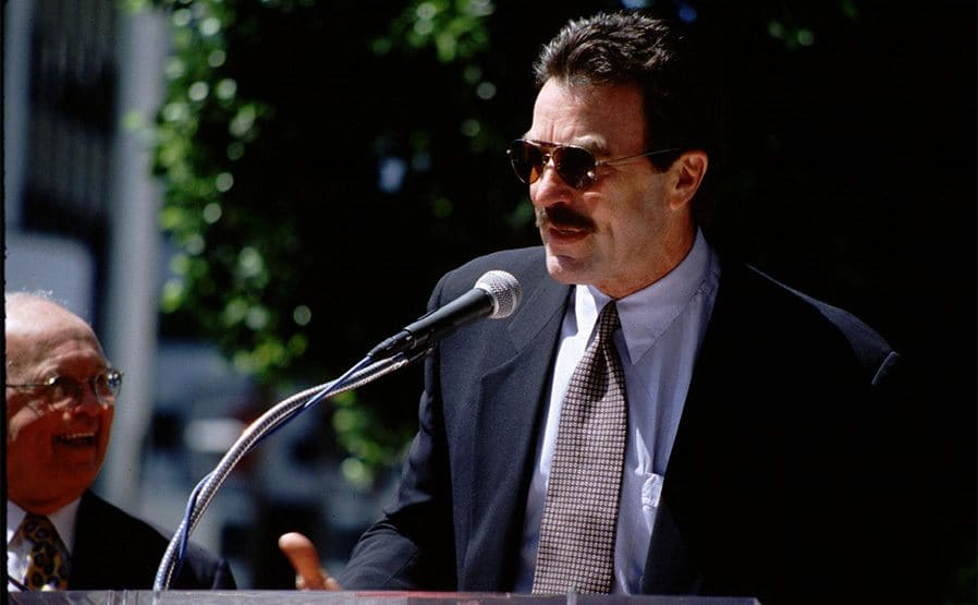 Tom Selleck standing outside on stage giving a speech r