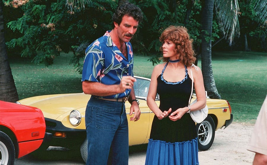 Tom Selleck and Jill St John standing in front of a yellow car