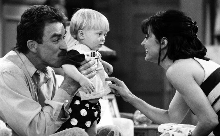 Tom Selleck holding up a baby with Courteney Cox on the TV show Friends.