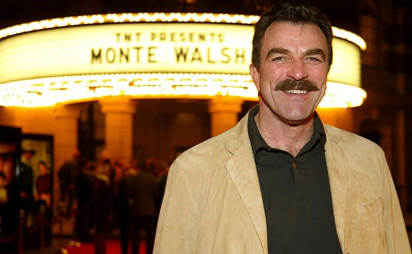 Tom Selleck in front of a sign for Monte Walsh