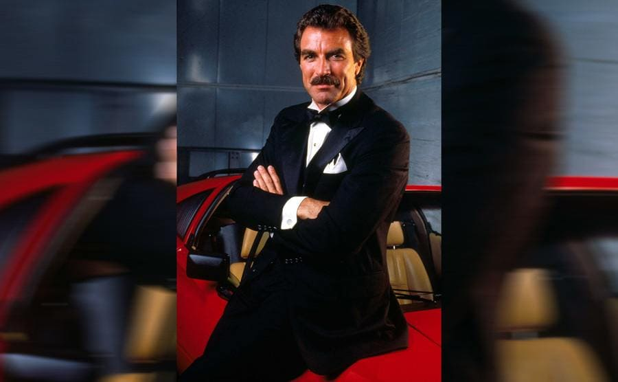 Tom Selleck in Magnum P.I. wearing a suit and leaning on the red car