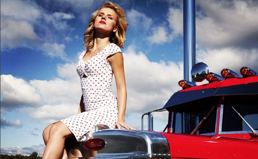 Agnes Olech sitting in a white dress with red polka dots on top of a red truck