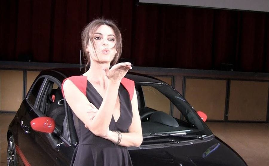 Catrinel Menghia blowing an air kiss while standing in front of a Fiat