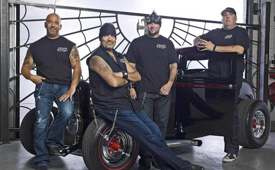Kevin Mack, Danny Koker, Horny Mike, and Scott Smith posing together in front of a custom hot rod