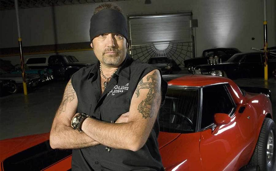 Danny Koker leaning on a red car