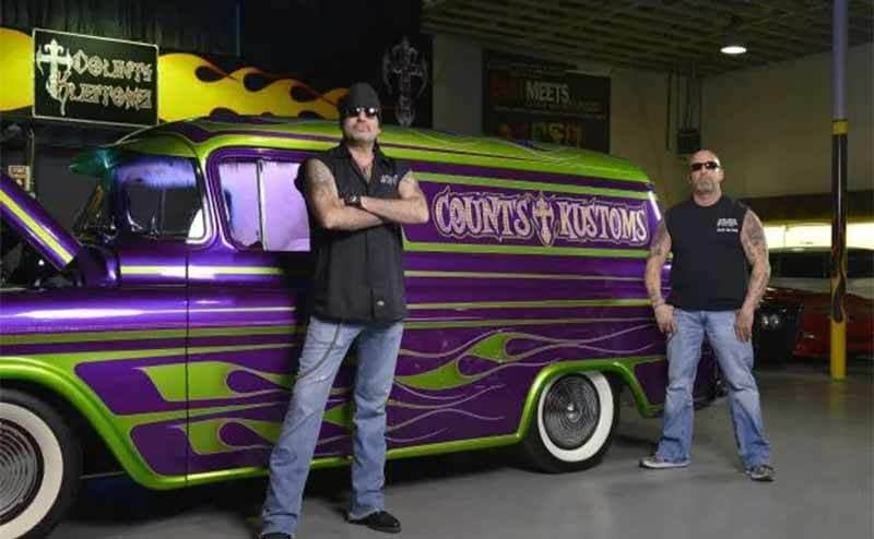Danny and Kevin standing in front of a car that is purple with green flames and says Counts Kustoms on it