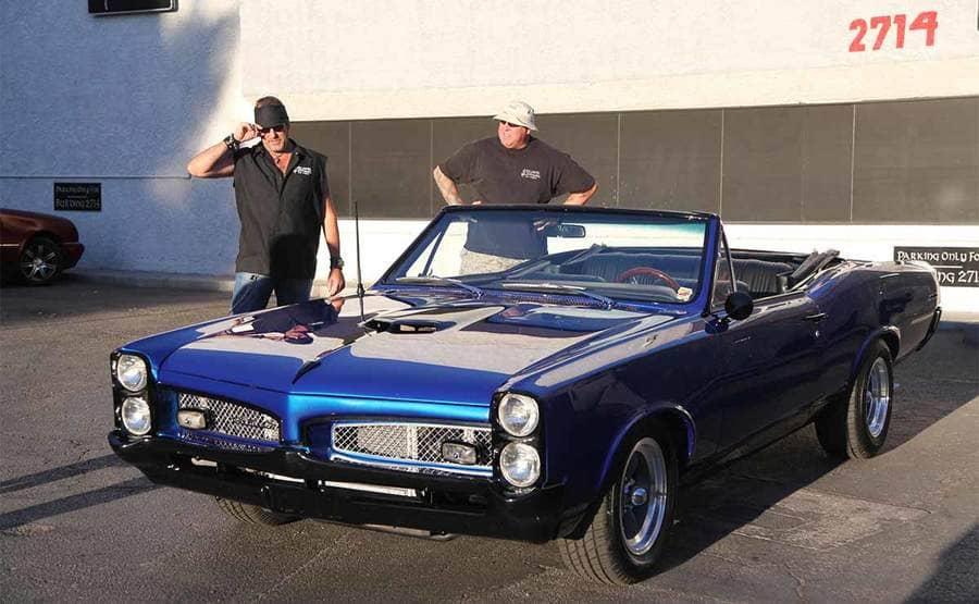 Danny Koker and Scott Smith looking at a royal blue Pontiac GTO convertible