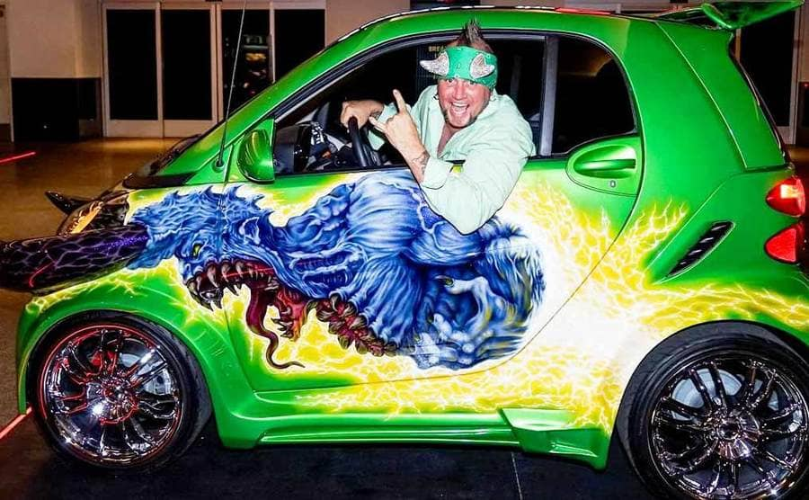 A smart car built up with new fancy rims and a green paint job with a blue monster on it