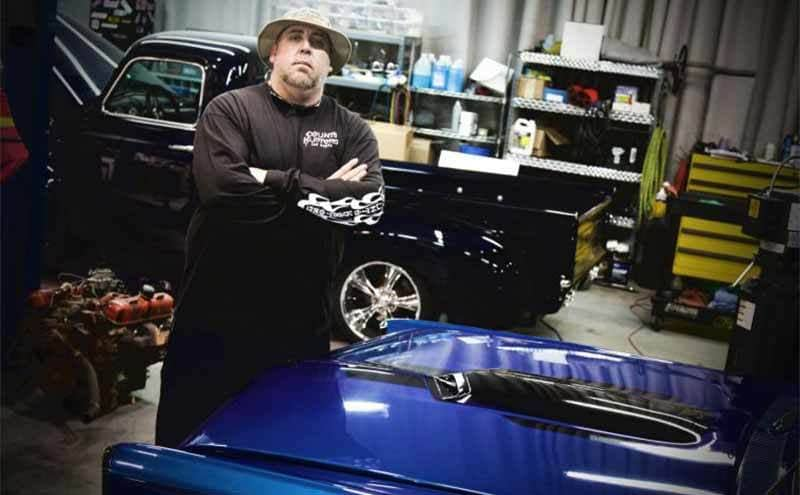 Scott Jones standing with his arms crossed in front of a royal blue car hood