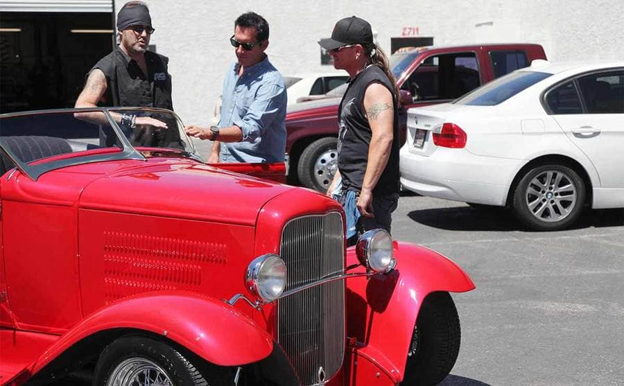 Danny Koker and Roli Szabo looking at an old red car