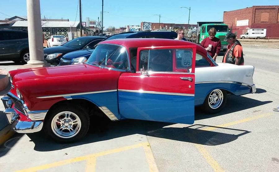 A red and blue car parked in a lot with people standing around it