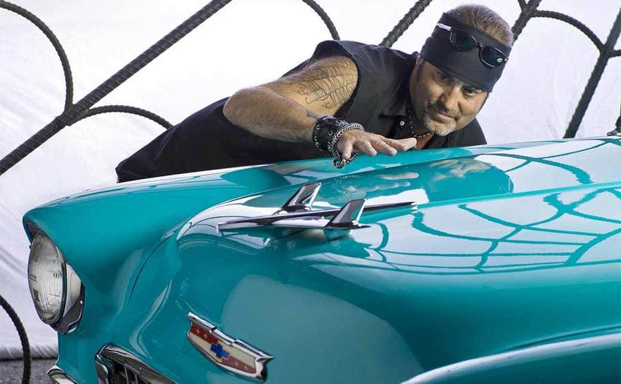 Danny Koker leaning down and inspecting the front of a teel car