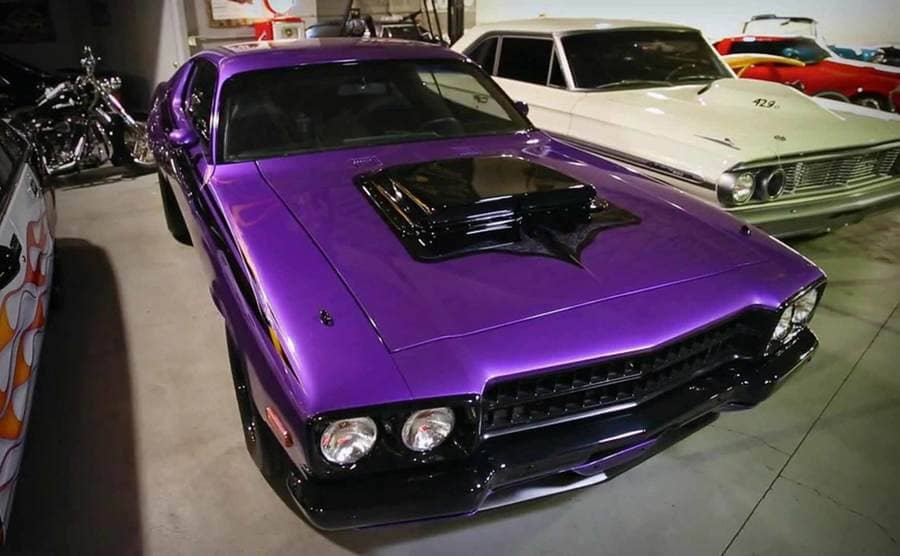 A purple car and others sitting around a parking lot