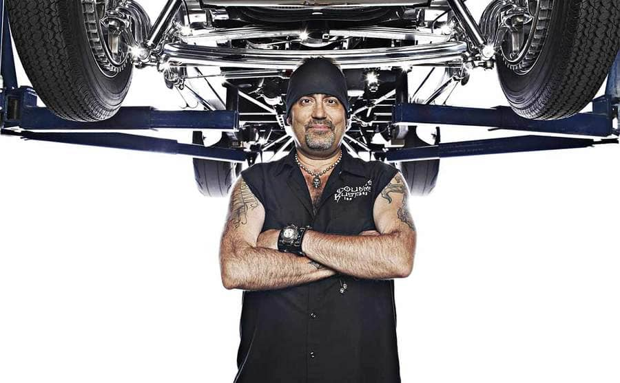 Danny Koker standing underneath the frame of a car which is lifted into the air