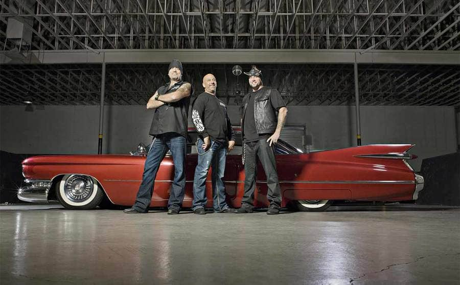 Danny Koker, Kevin Mack, and Horny Mike posing in front of a red Cadillac