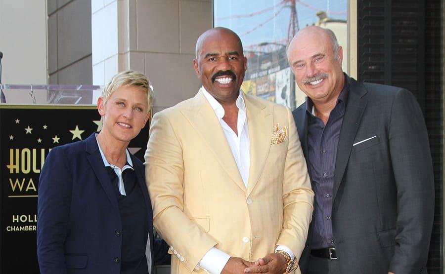 Ellen DeGeneres, Steve Harvey, and Dr. Phil posing together on the Hollywood Walk of Fame when Steve Harvey received his star.
