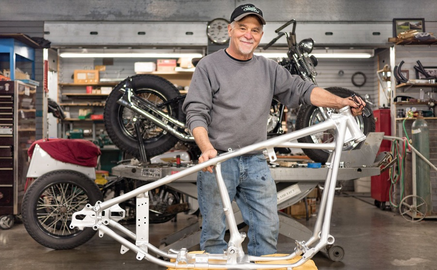 Dale Walksler standing over a bike frame in the garage