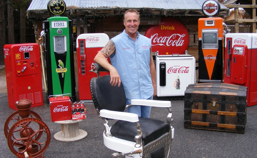 Rick standing in front of an old barbers chair with old gas pumps and coca-cola machines behind him