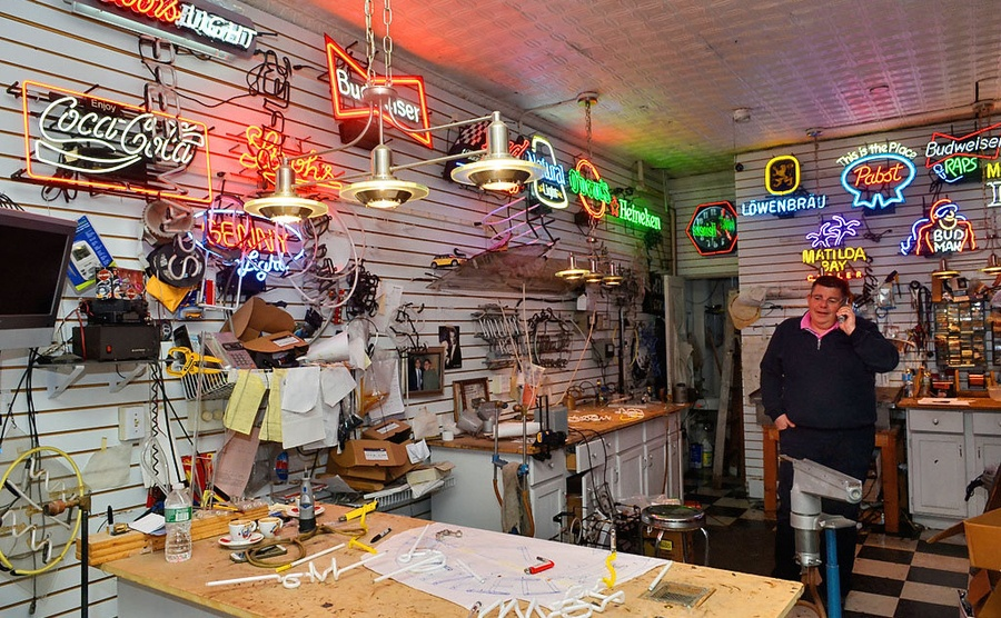 Howie Cohen talking on the phone in his neon lights shop