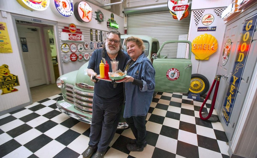 Bob Halliday with his wife posing in front of a vintage car with neon signs everywhere