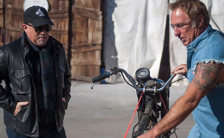Rick helping Billy Joel with an old motorcycle