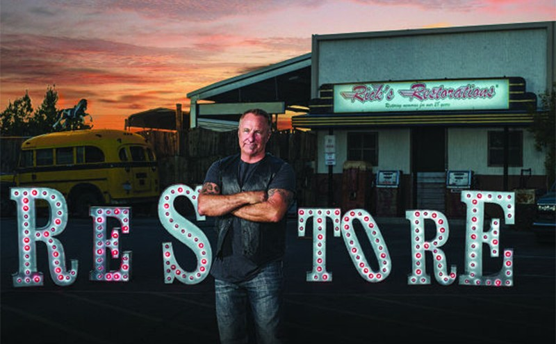 Rick standing in front of a sign that says Restore