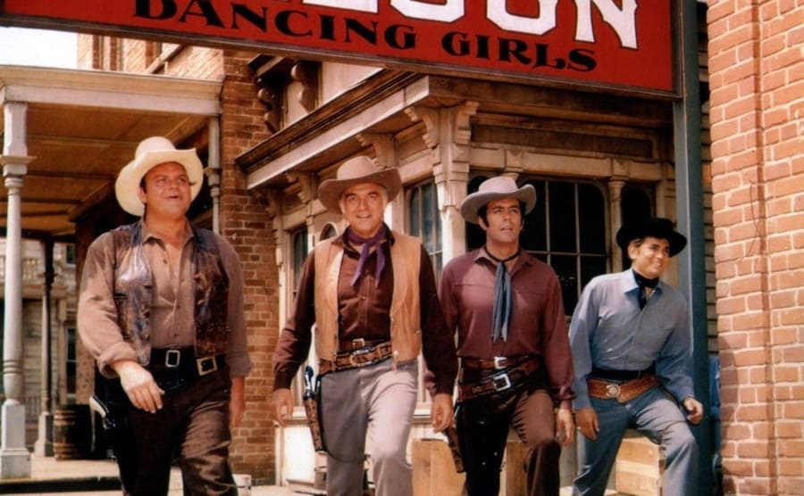 Dan Blocker, Pernell Roberts, Michael Landon, and Lorne Greene posing together in front of a sign that says 'Saloon dancing girls'