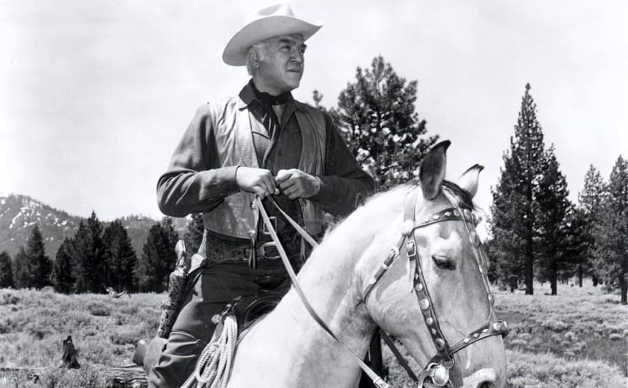 Lorne Greene riding a horse on the show Bonanza