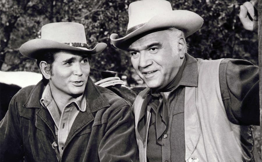 Michael Landon and Lorne Greene posing behind a large wooden fence on the show Bonanza