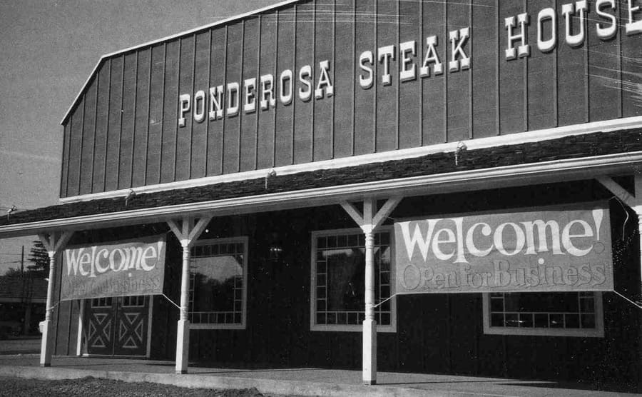 A photograph of the Ponderosa Steak House with Welcome signs tied outside