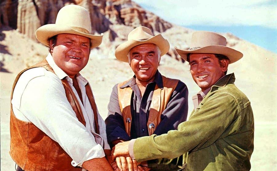 Dan Blocker, Lorne Greene, and Michael Landon putting their hands together in an open desert