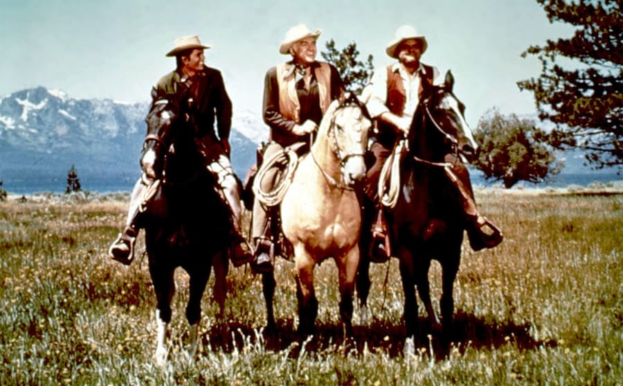 Michael Landon, Lorne Greene, and Dan Blocker riding horses with a view behind them of open field and mountain