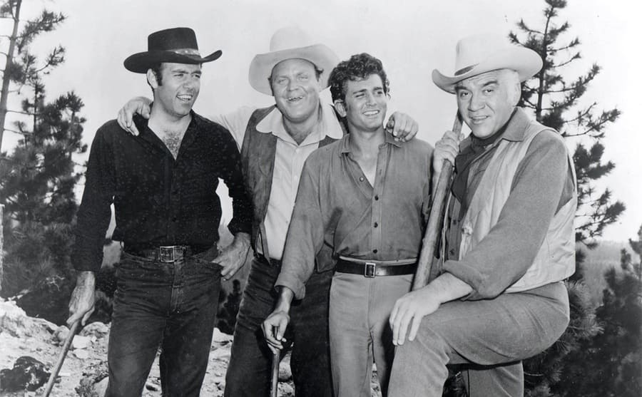 Pernell Roberts, Dan Blocker, Michael Landon, and Lorne Greene posing together in the woods