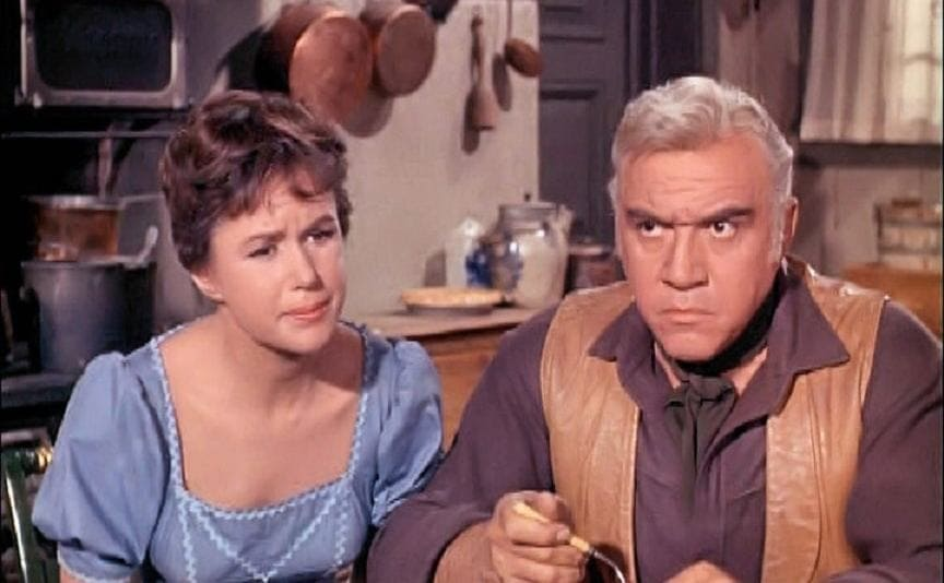 Nancy Rennick and Lorne Greene sitting at the kitchen table while Lorne eats in a scene from Bonanza