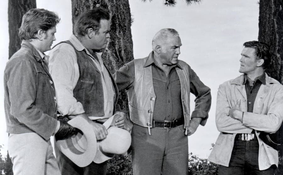 Michael Landon, Dan Blocker, Lorne Greene, and David Canary having a discussion in the woods