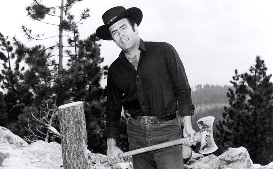 Pernell Roberts holding an ax next to a cut-down tree