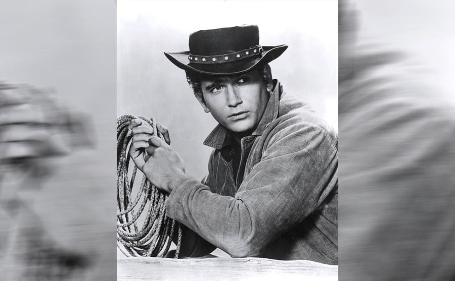 Michael Landon posing with a rope and cowboy hat
