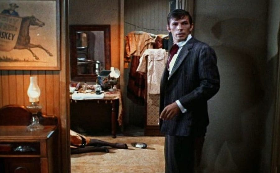 Leonard Nimoy standing in a doorway with a woman's legs sprawled out on the floor