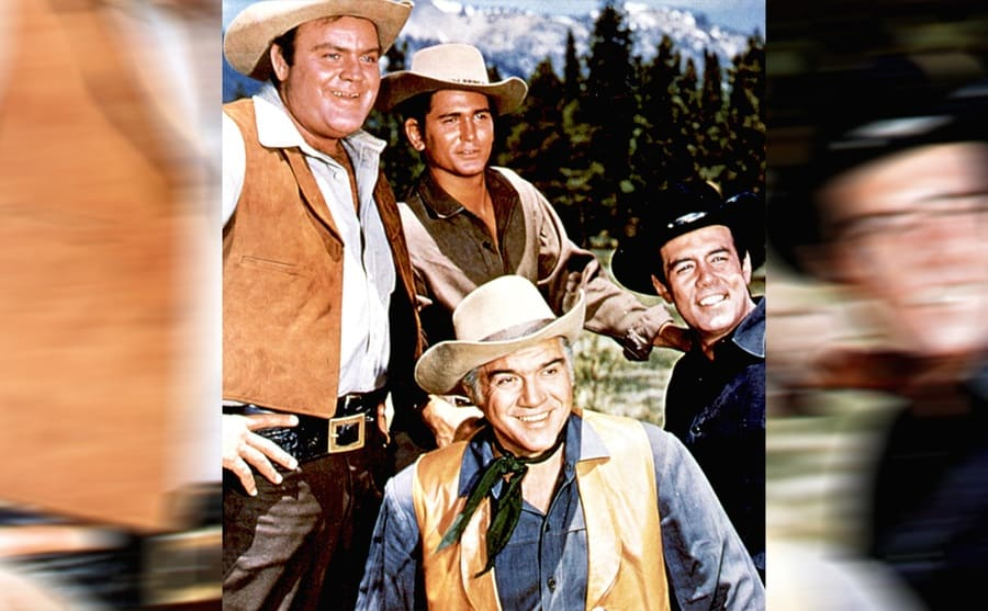 Dan Blocker, Michael Landon, Lorne Greene, and Pernell Roberts posing together with trees and mountains behind them