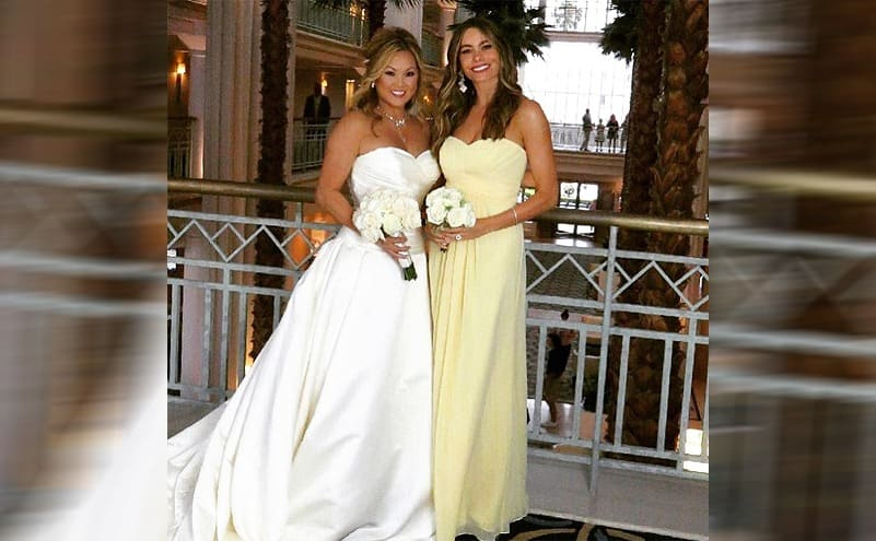 Sophia Vergara wearing a yellow strapless dress while posing with her friend on her wedding day