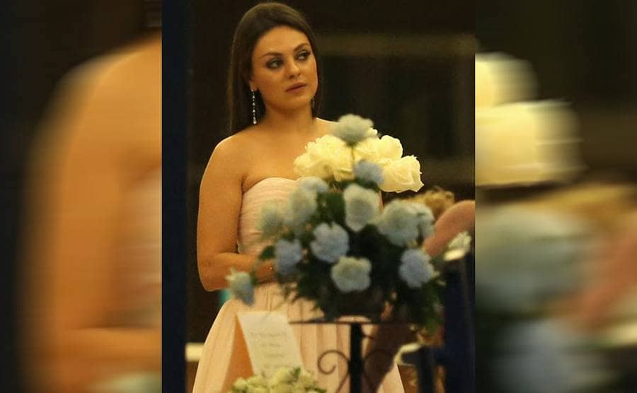 Mila Kunis in a pink strapless dress standing behind a bouquet of flowers