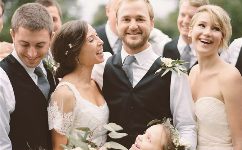 Jennifer Lawrence laughing with her sister and sister's husband on their wedding day surrounded by loved ones